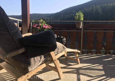 Luxus-Ferienwohnung Bergsee: Der Balkon mit bequemen Liegestühlen und Ausblick auf den Schwarzwald