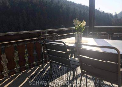 Luxus-Ferienwohnung Bergsee: Der sonnige Balkon mit Tisch und Stühlen zum gemütlich draußen sitzen