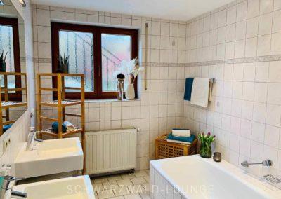 Luxus-Ferienwohnung Bergsee: Das moderne Badezimmer mit Badewanne und Fenster