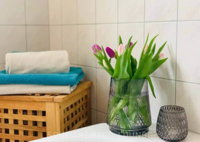 Luxus-Ferienwohnung Bergsee: Detail aus dem Badezimmer: Wäschekorb und Blumenschmuck