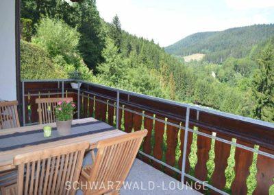 Wellness-Apartment Waldwiese: Der Balkon mit Tisch und bequemen Stühlen mit herrlichem Ausblick auf den Schwarzwald