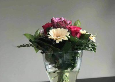 Luxus-Ferienwohnung Bergsee: Detail aus dem Essplatz in der Küche: Esstisch mit Blumenstrauß