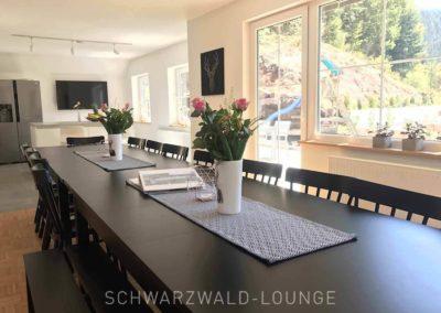 Schwarzwald-Ferienhaus Lohmühle: Das Esszimmer mit Blumen auf dem langen Tisch und Blick auf den Garten