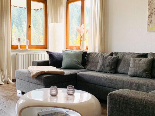 Ferien-Appartment Waldwiese: Wohnzimmer mit Sofa und Fenster mit Blick auf den Wald