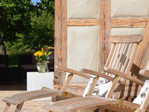 Ferien-Chalet Lindembuch: Terrasse mit Liegestühlen vor einer Fachwerk-Mauer