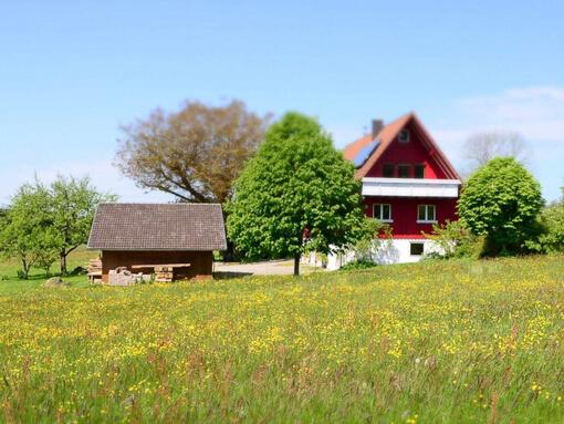 Ferienhaus Brestenberg umgeben von Wiesen und Bäumen