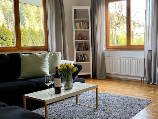 Ferienwohnung Kinzigtal: Wohnzimmer mit Sofa, Blumen und Fenster mit Blick auf den Wald