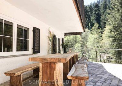 Schwarzwald-Ferienhaus Lohmühle: Die überdachte Terrasse mit Tisch und Bänken aus Holz