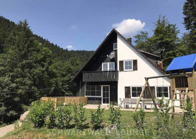Das Schwarzwald-Ferienhaus Lohmühle von außen mit Garten und Spielplatz