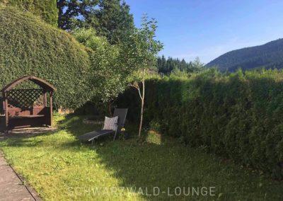 Ferienwohnung Kinzigtal: Der Garten mit Wiese, einem kleinen Pavillon und einem Liegestuhl, geschützt von einer Hecke
