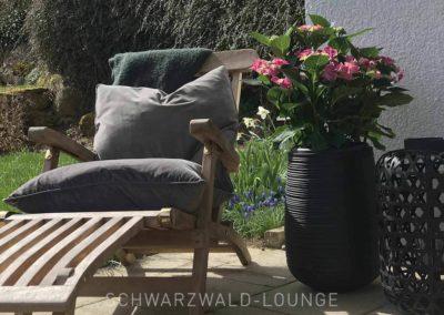 Ferienwohnung Kinzigtal: Ein gemütlicher Liegestuhl mit Kissen und Decken zum Entspannen im Garten