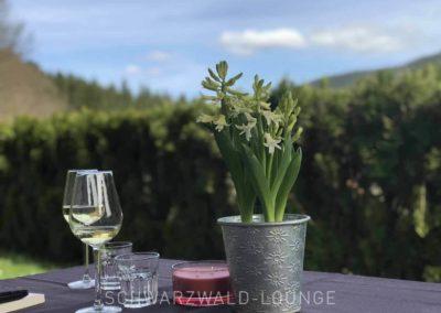 Ferienwohnung Kinzigtal: Der Tisch auf der Terrasse mit Wein und Blumenschmuck mit Wald im Hintergrund