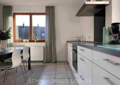 Luxus-Ferienwohnung Bergsee: Die Küche mit Essplatz und Blick aus dem Fenster