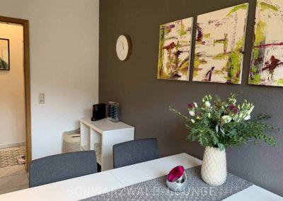 Ferienwohnung Kinzigtal: Der Essplatz vom Fenster aus gesehen mit frischen Blumen auf dem Tisch