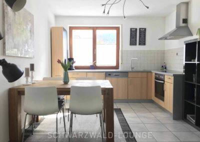 Wellness-Apartment Waldwiese: Blick in die Küche mit Essbereich und Fenster ins Grüne