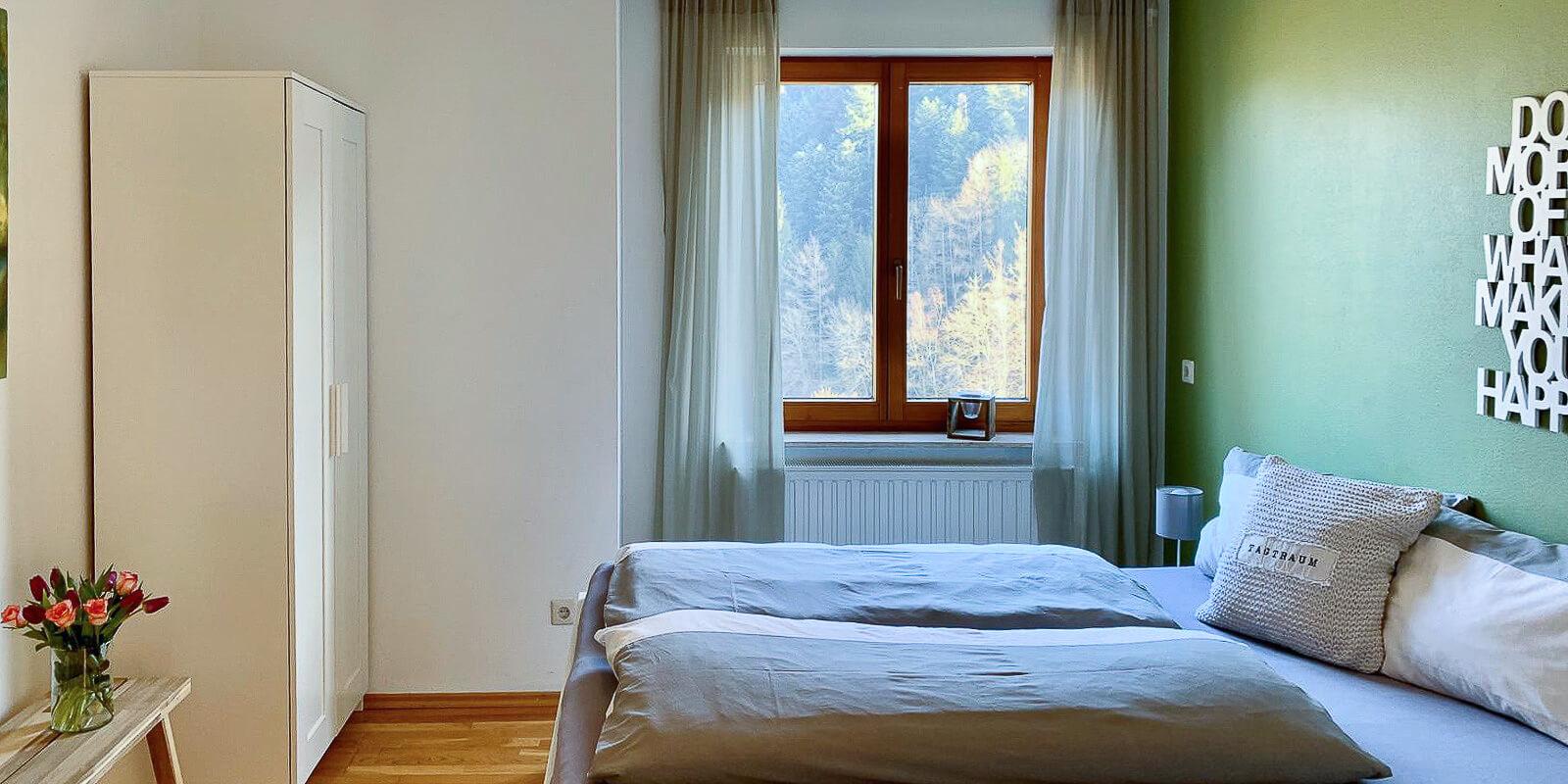 Luxus-Ferienwohnung Bergsee: Schlafzimmer mit Blick auf den Wald