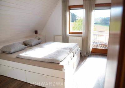 Ferienhaus Brestenberg: Schlafzimmer mit Balkon im Obergeschoss mit Doppelbett