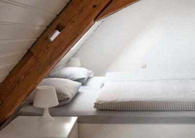 Ferienhaus Brestenberg: Das kleine Schlafzimmer im Obergeschoss mit Fachwerkbalken und Doppelbett