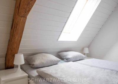 Ferienhaus Brestenberg: Das kleine Schlafzimmer im Obergeschoss mit Fachwerkbalken und Dachfenster