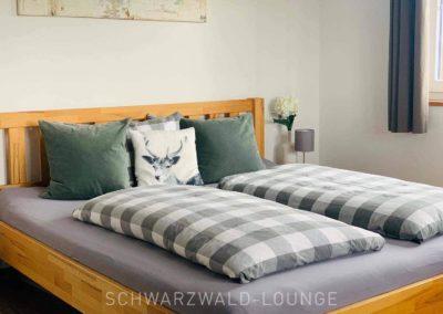 Chalet Lindenbuch: Das Doppelbett in Schlafzimmer 2 mit Zierkissen