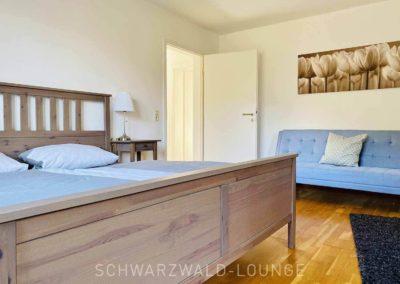 Luxus-Ferienwohnung Bergsee: Das erste Schlafzimmer mit Doppelbett und Schlafsofa im Hintergrund