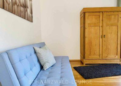 Luxus-Ferienwohnung Bergsee: Das Schlafsofa im ersten Schlafzimmer mit Blick auf den schönen Bauernschrank