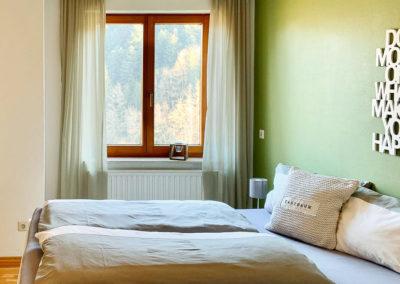 Luxus-Ferienwohnung Bergsee: Das zweite Schafzimmer mit Doppelbett und Blick auf den Wald