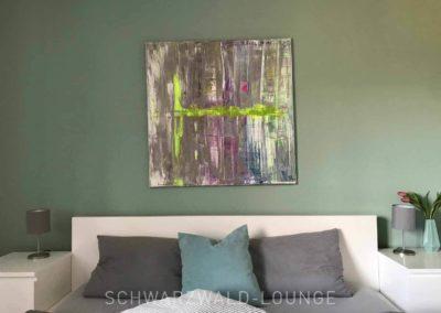 Wellness-Apartment Waldwiese: Das Wohnzimmer mit der gemütlichen Couch, die Fenster mit Blick auf den Wald im Hintergrund