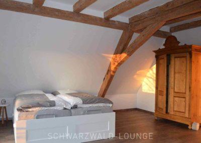 Ferienhaus Brestenberg: das großen Schlafzimmer im Obergeschoss mit alten Fachwerk-Sichtbalken und einem stilvollen Bauernschrank