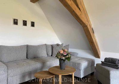 Ferienhaus Brestenberg: Sofa-Ecke unter Fachwerk-Balken im großen Schlafzimmer im Obergeschoss