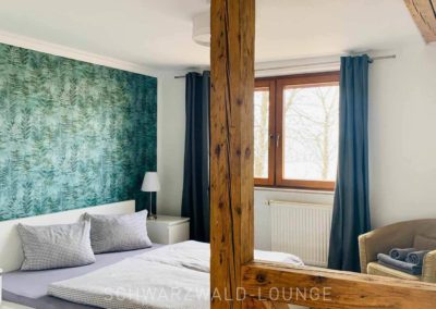 Ferienhaus Brestenberg: Schafzimmer 3 im Erdgeschoss mit Fachwerkbalken und Doppelbett neben dem Fenster