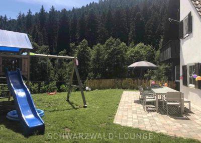 Schwarzwald-Ferienhaus Lohmühle: Spielplatz und Terrasse im sonnigen Garten
