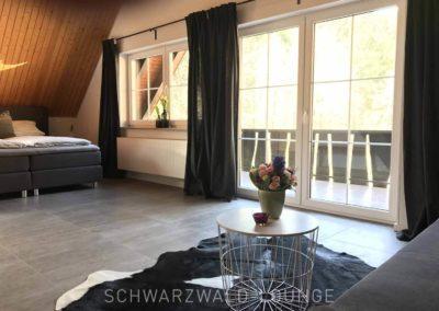 Schwarzwald-Ferienhaus Lohmühle: Die große Suite mit Doppelbett, Sofa und Balkon im Obergeschoss