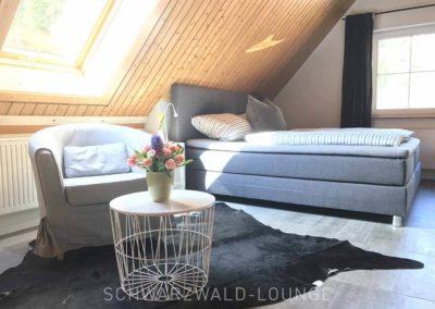 Schwarzwald-Ferienhaus Lohmühle: Die große Suite mit Doppelbett und Dachfenster und Fernseher an der Wand