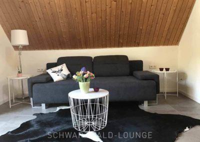 Schwarzwald-Ferienhaus Lohmühle: Das Sofa mit Tischchen in der großen Suite unter dem Dach