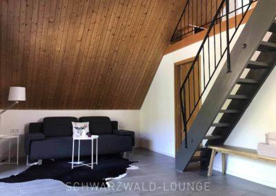 Schwarzwald-Ferienhaus Lohmühle: Das Sofa in der großen Suite mit der offenen Treppe zur Empore