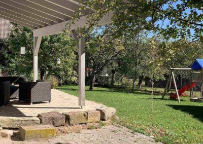 Chalet Lindenbuch: Der überdachte Teil der Terrasse mit Blich auf den Garten mit Spielplatz