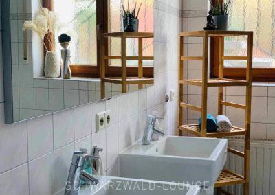 Luxus-Ferienwohnung Bergsee: Das Bad mit zwei Waschbecken und Regal aus Holz