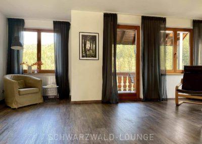 Luxus-Ferienwohnung Bergsee: Das geräumige Wohnzimmer mit Türe zum überdachten Balkon und Leseecke