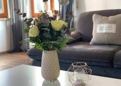 Luxus-Ferienwohnung Bergsee: Detail aus dem Wohnzimmer: Blumenstrauß auf dem Couchtisch vor der Sitzgruppe