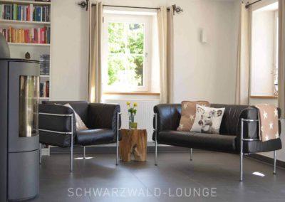 Chalet Lindenbuch: Das Wohnzimmer mit Sitzecke unter Fenstern und Kamin