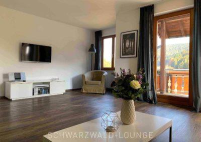 Luxus-Ferienwohnung Bergsee: Das große Wohnzimmer mit Zugang zum Balkon, Leseecke und Fernseher