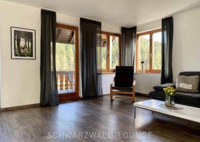 Luxus-Ferienwohnung Bergsee: Das Wohnzimmer mit Balkontür und Fenstern und Blick auf den Wald