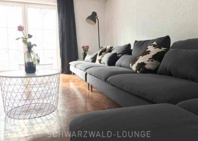 Schwarzwald-Ferienhaus Lohmühle: Die große Couch mit Tischchen und Blick in den Garten im Erdgeschoss