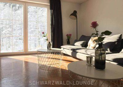 Schwarzwald-Ferienhaus Lohmühle: die große Couch mit zwei Tischen und Blick in den Garten im Winter
