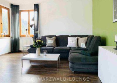 Luxus-Ferienwohnung Bergsee: Das helle Wohnzimmer mit dem großen, gemütlichen Ecksofa