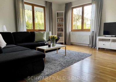 Ferienwohnung Kinzigtal: Blick ins Wohnzimmer mit zwei großen Fenstern über Eck und einer modernen Eck-Couch und Fernseher