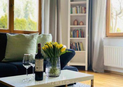 Ferienwohnung Kinzigtal: Detail aus dem Wohnzimmer, der Couchtisch mit frischen Blumen und Wein
