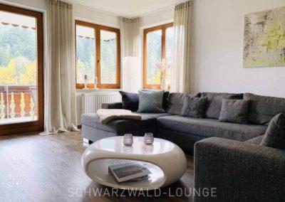 Wellness-Apartment Waldwiese: Das Wohnzimmer mit der gemütlichen Couch und dem Zugang zum Balkon mit Blick auf den Wald